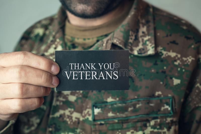 Soldier holding card Thank You Veterans. stock photo