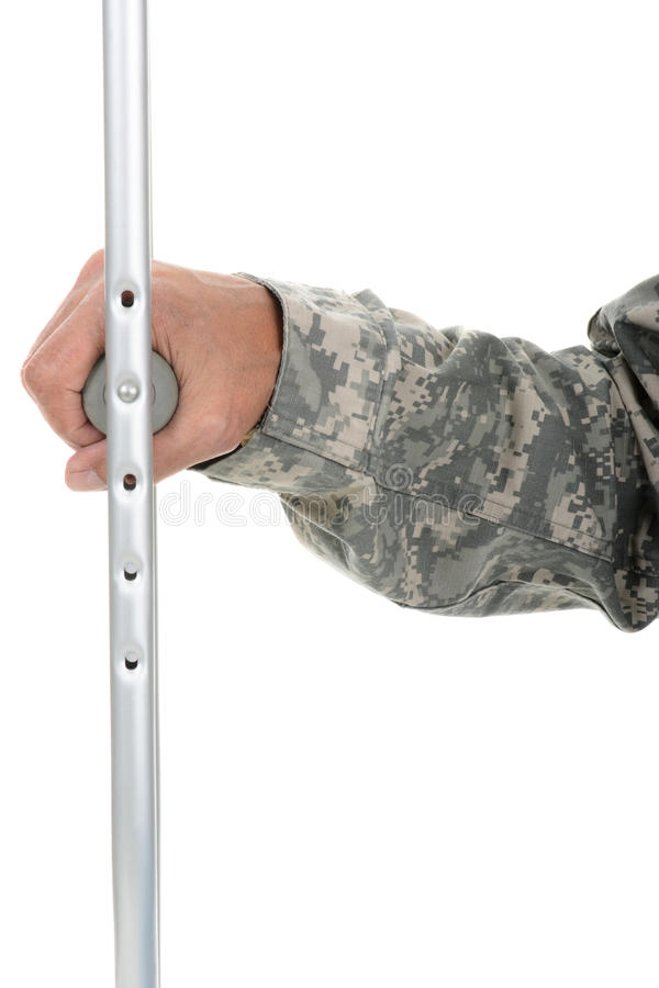 Soldier Holding Crutch. Closeup of a soldier holding onto the hand grip of a crutch. Only his hand and arm are visible. The man is wearing camouflage fatigues royalty free stock photos