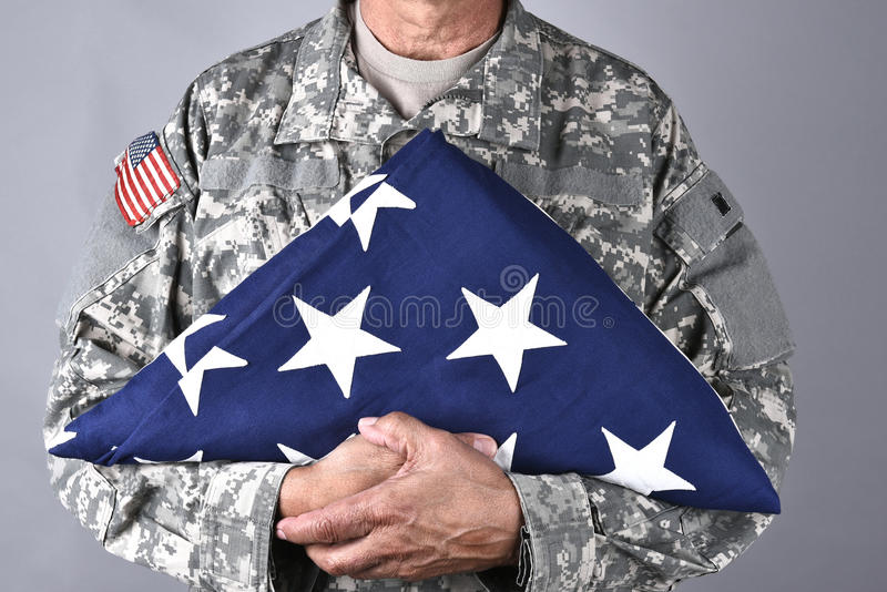 Soldier Holding Folded Flag. Closeup of an American Soldier in fatigues holding a folded flag in front of his torso. The man is unrecognizable stock photography