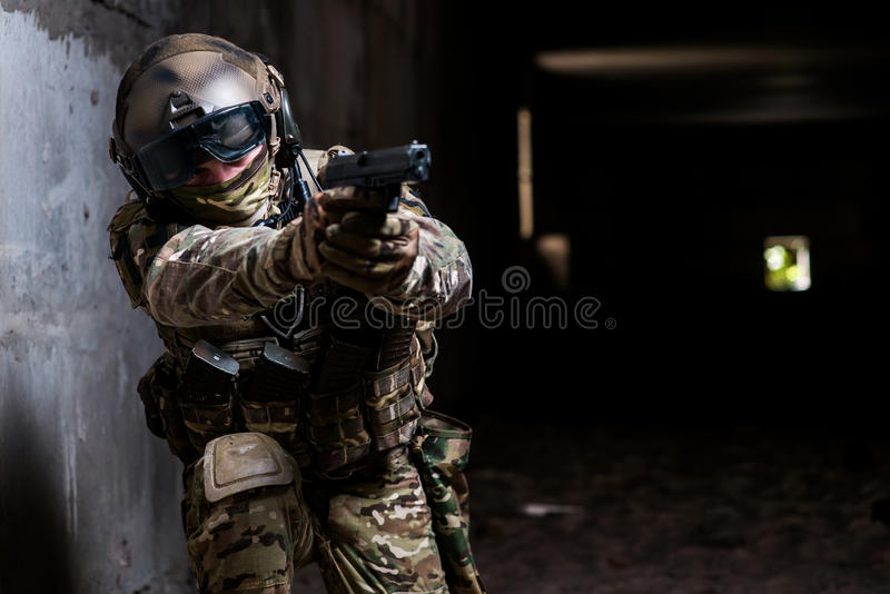 Soldier holding a gun in his hand and aiming stock photo