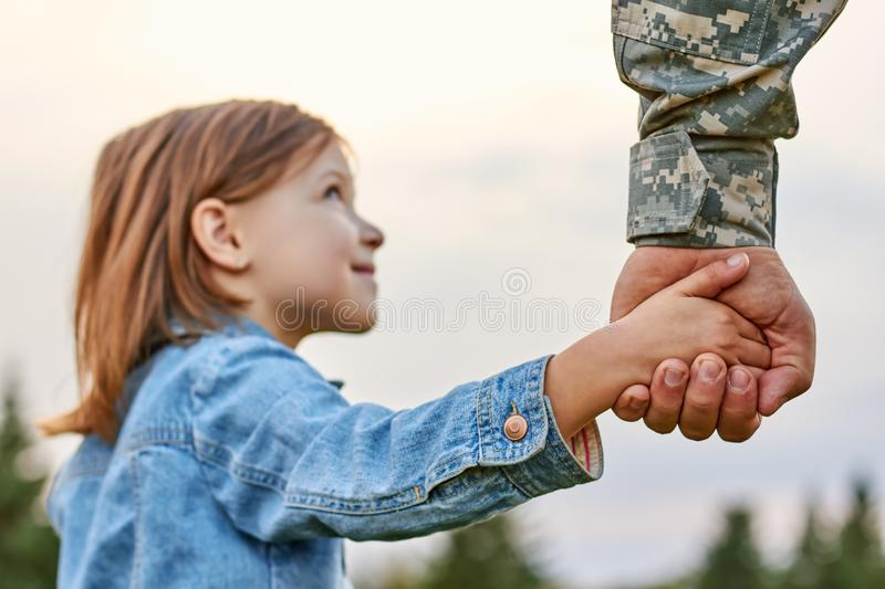 Soldier holding hand of little girl, close up. royalty free stock photo