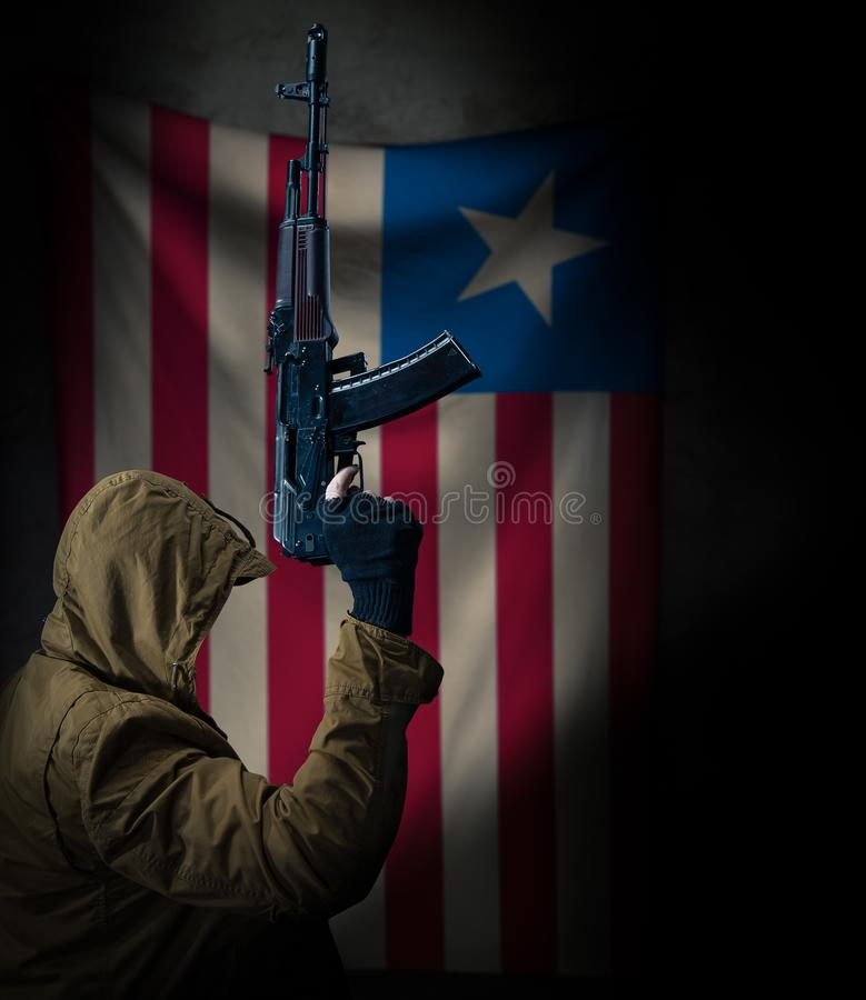 Soldier holding machine gun with national flag on background stock photo