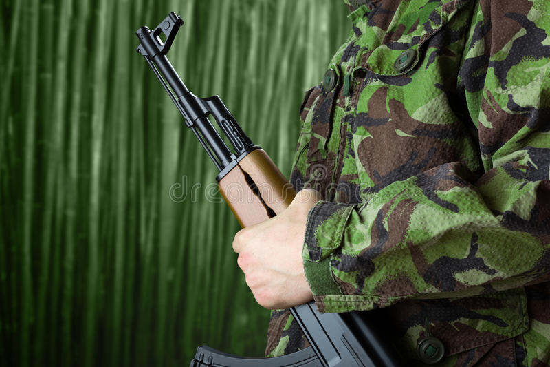 Soldier holding rifle AK-47 royalty free stock photo
