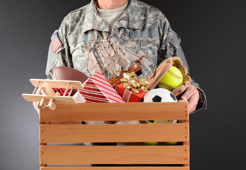 Soldier Holding Toy Drive Box. Closeup of a soldier in fatigues holding a wooden box full of toys and sports equipment for a holiday charity drive. Horizontal royalty free stock images