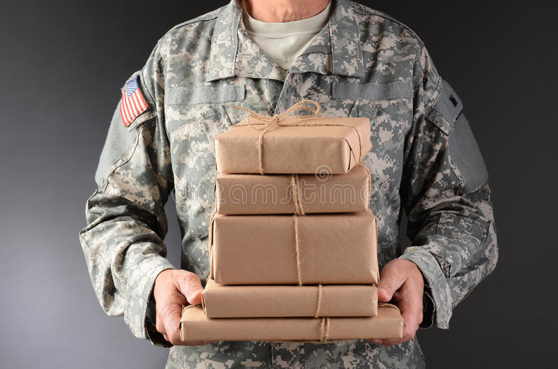 Soldier Holding Toy Drive Box. Closeup of a soldier in fatigues holding a wooden box full of toys and sports equipment for a holiday charity drive. Horizontal stock photos