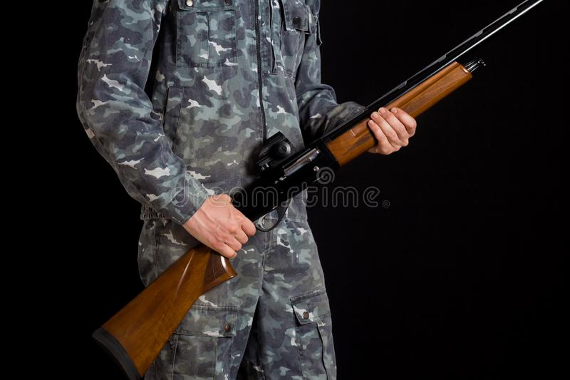 Soldier or hunter on a black background, isolated, copy space. Young man with a gun. A soldier in military uniform with a shotgun royalty free stock photos