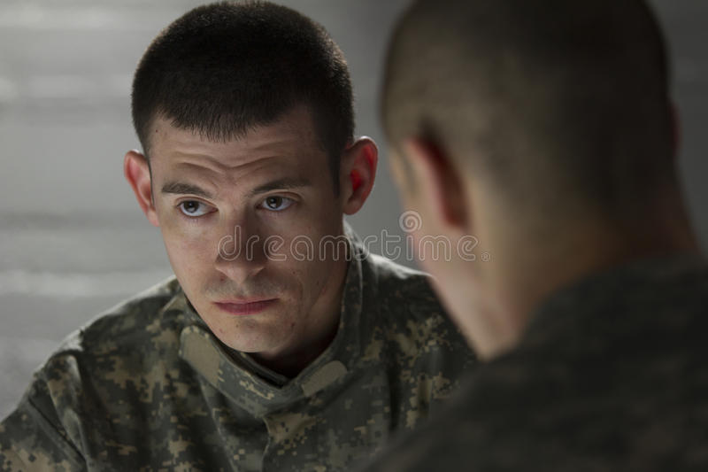 Soldier looks somber while being consoled by peer, horizontal stock image