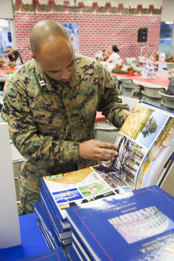 Soldier looks at Visions of America book at Christmas dinner, Wounded Warrior Center, Camp Pendleton, North of San Diego royalty free stock image