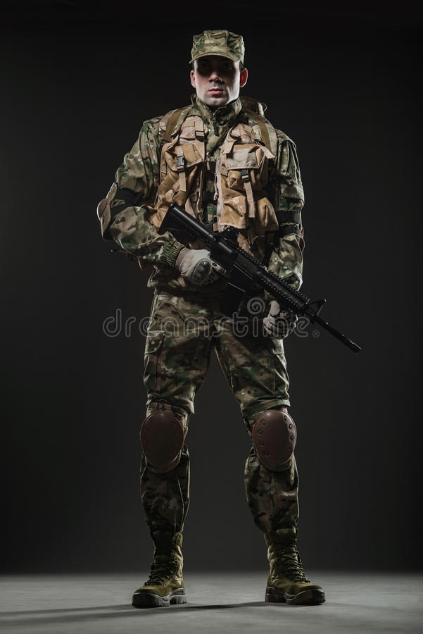 Soldier man hold Machine gun on a dark background. Military, war, conflict, soldiers - Special forces soldier man hold Machine gun on a dark background. Military royalty free stock image
