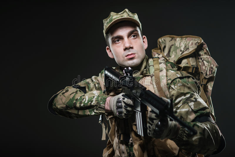 Soldier man hold Machine gun on a dark background. Military, war, conflict, soldiers - Special forces soldier man hold Machine gun on a dark background. Military royalty free stock photo