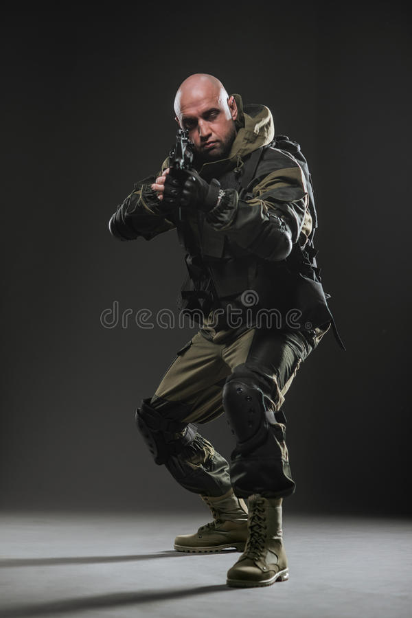 Soldier man hold Machine gun on a dark background. Military, war, conflict, soldiers - Special forces soldier man hold Machine gun on a dark background. Military royalty free stock photography