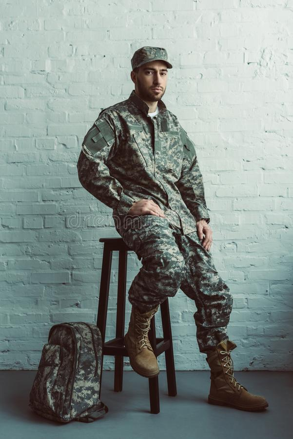 Soldier in military uniform sitting on chair against white. Brick wall royalty free stock images