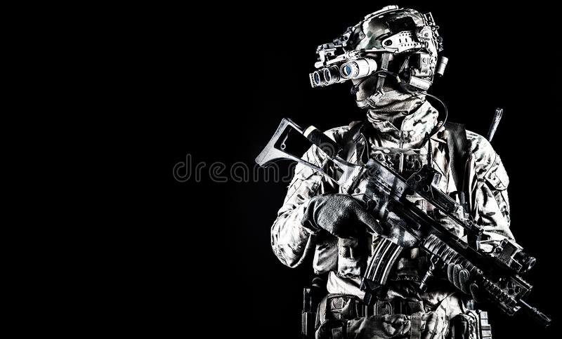 Soldier in night vision device on black background. Half length portrait of army special forces rifleman, commando elite soldier equipped radio tactical headset stock photography