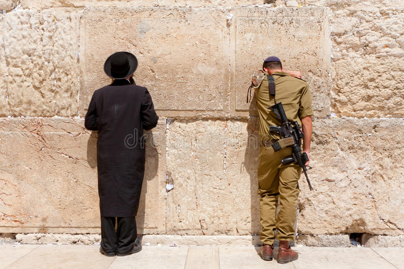 Soldier and orthodox jewish man pray at the western wall, Jerusalem stock images
