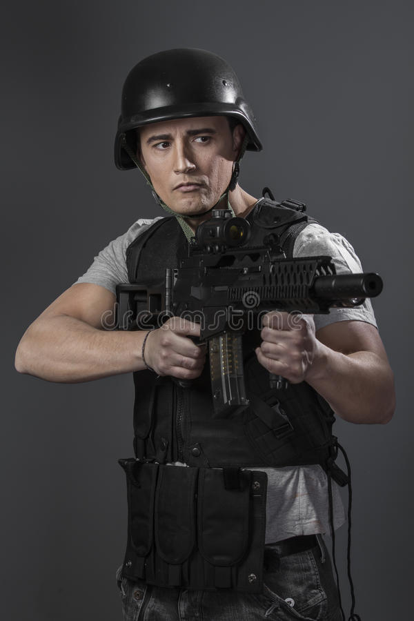 Soldier, paintball sport player wearing protective helmet aiming stock photo