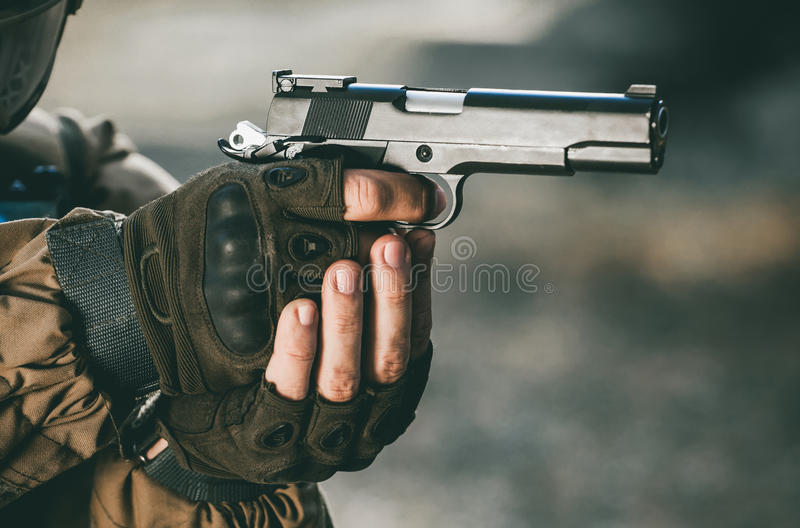 The soldier in the performance of tasks in camouflage and protective gloves holding a pistol with the hammer cocked takes aim for royalty free stock photo