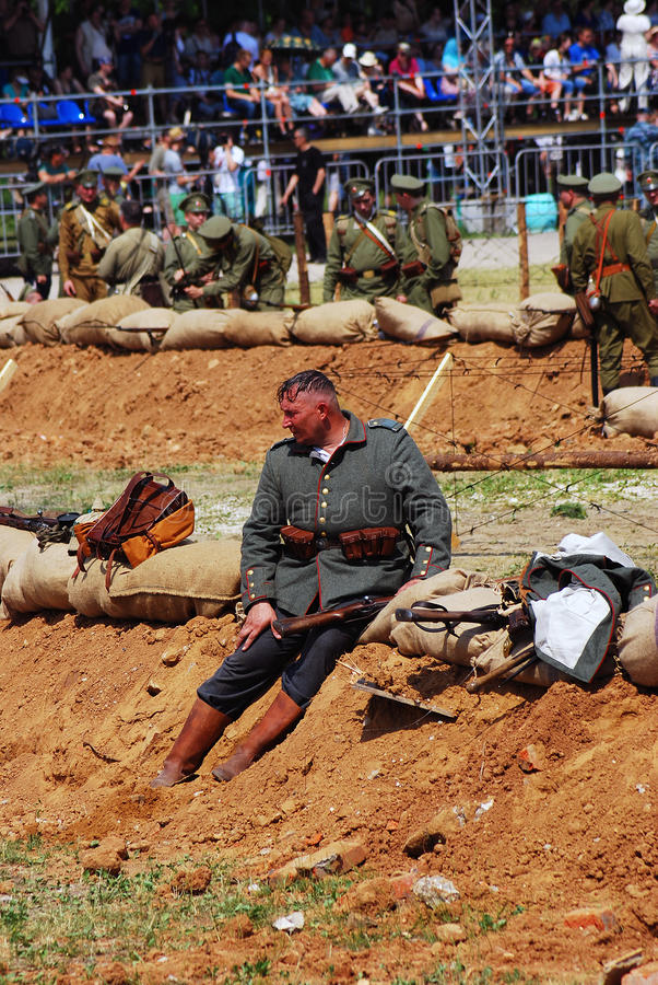 A soldier-reenactor sits on the ground, he looks tired. stock images