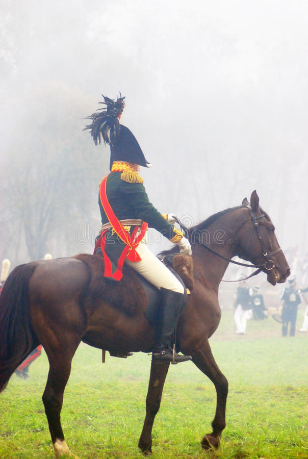 A soldier rides a brown horse. stock photography