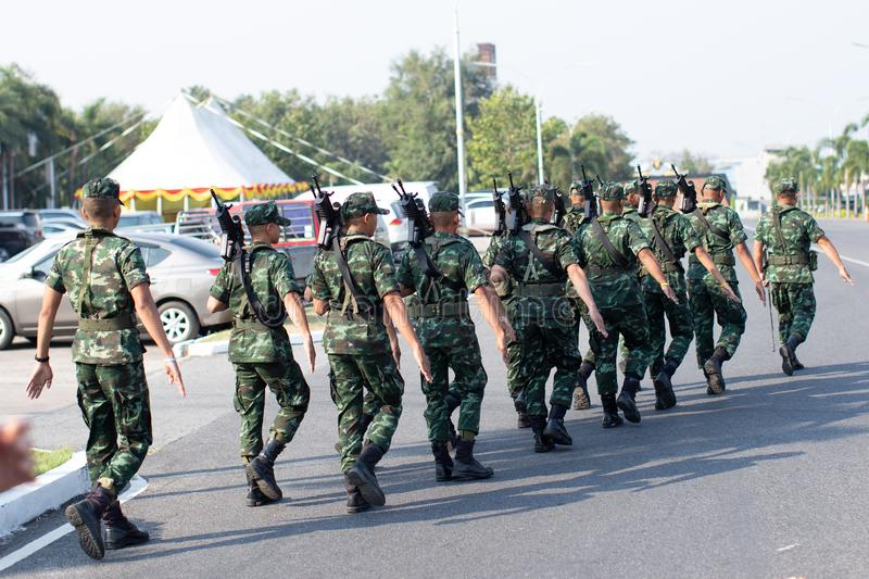 soldier with rifle gun long range patrolling on city. Group of Soldiers marching on the asphalt road. The security unit is checkin stock photography