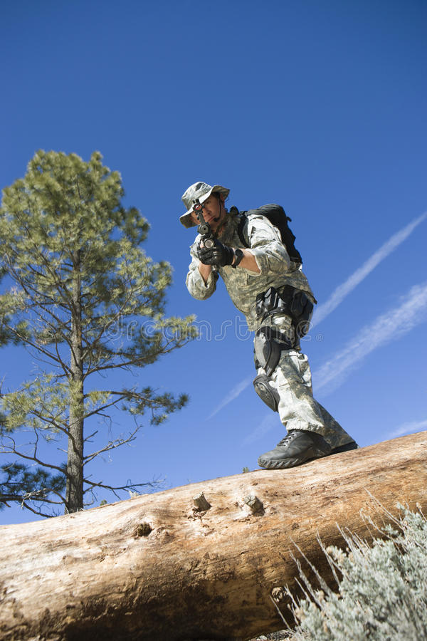 Soldier With Rifle Standing On Tree Trunk stock image
