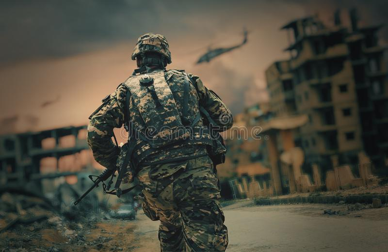 Soldier running in destroyed city stock image