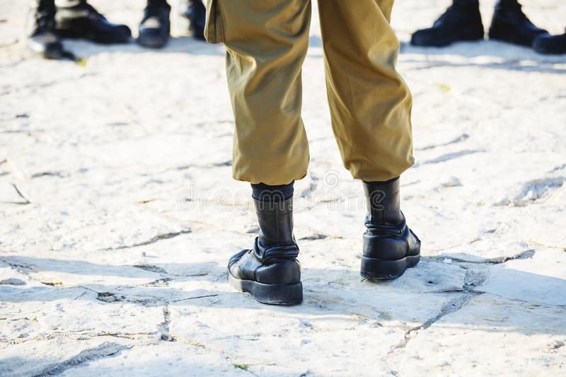 The soldier`s footwear of the Israeli army which is put on legs in clear sunny day royalty free stock photography