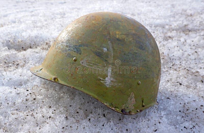 Soldier`s helmet lying on the snow stock photos