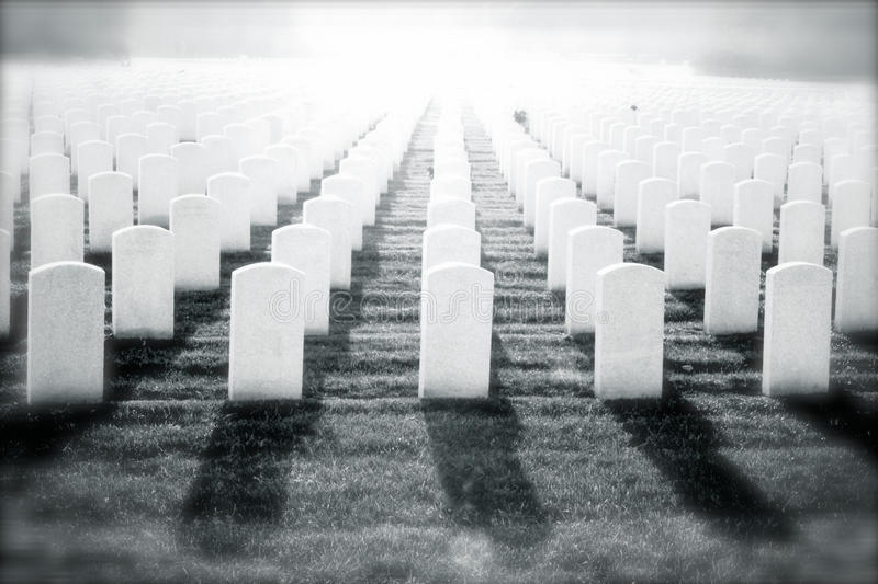 Soldier's Passage. Manipulated black and white image of white gravestones in a military cemetery with bright white light, conveying sacrifice, and spiritual stock photo