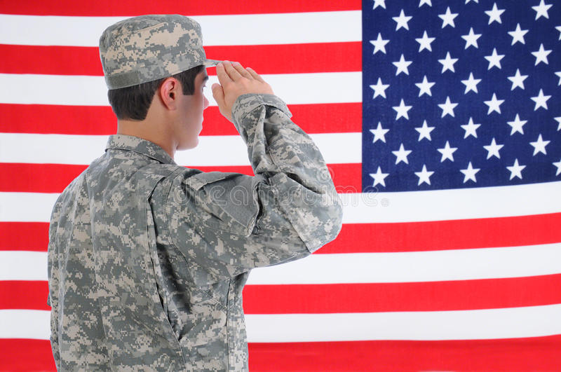 Soldier Saluting American Flag. Closeup of a young American Soldier in Fatigues saluting the Flag. Flag fills the frame and is out of focus. Man is seen from stock photos