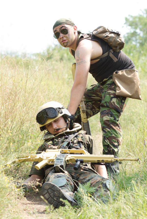 Soldier saves his wounded partner stock photos