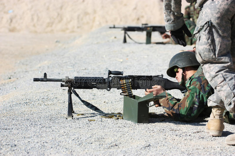 Soldier shooting. An Afghanistan soldier shooting with M240 machine-gun, during training exercise on a range, with US soldier mentoring him stock photos
