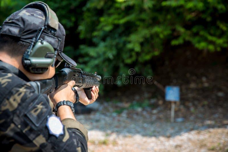soldier shooting rifle gun to target. Mature man aiming with gun at combat training. stock photos
