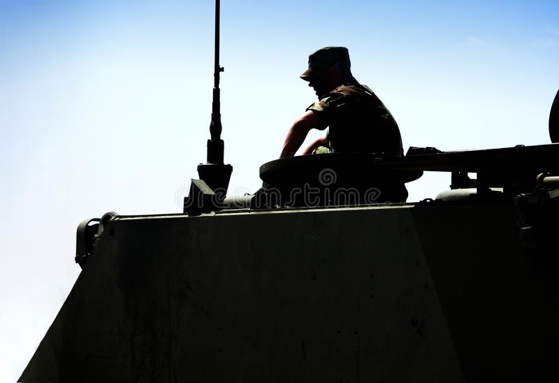 SOLDIER SITTING ON MILITARY VEHICLE IN SILHOUETTE WITH BLUE SKY. Soldier profile sitting on military vehicle in silhouette with clear blue sky in background stock images