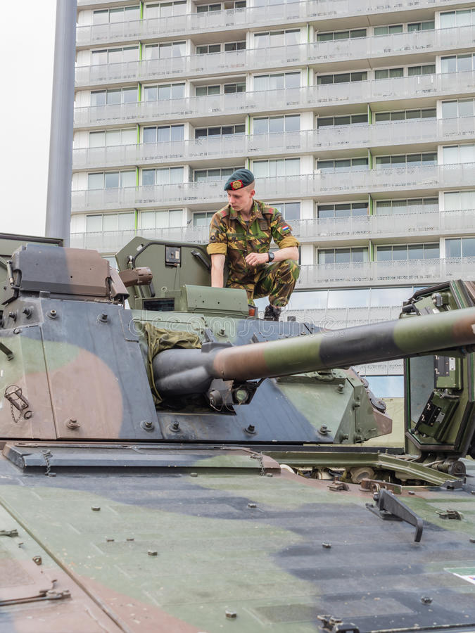 Soldier sitting on tank. ALMERE, NETHERLANDS - 23 APRIL 2014: Soldier sitting on a Dutch military armored fighting vehicle on display during the National Army stock photography