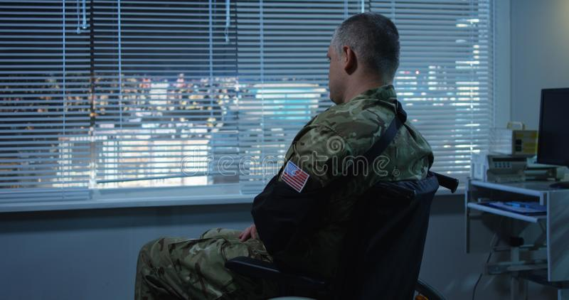 Soldier sitting in wheelchair in hospital. Medium shot of injured soldier sitting in wheelchair and looking through window in hospital room stock photos