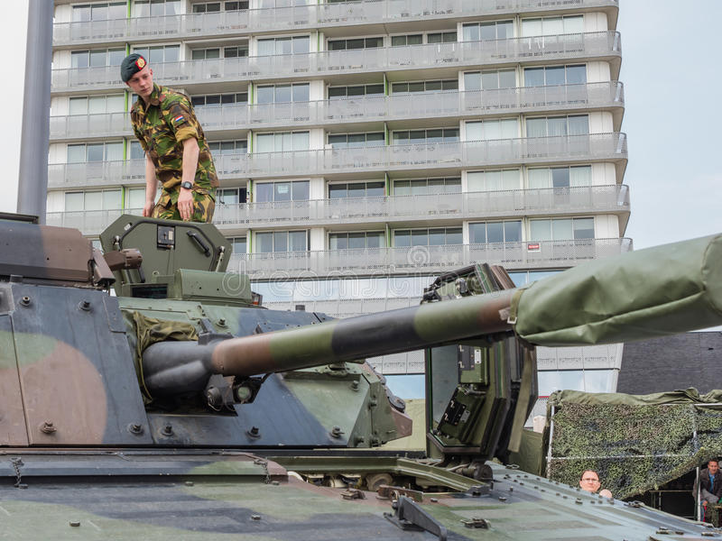 Soldier standing on tank. ALMERE, NETHERLANDS - 23 APRIL 2014: Soldier standing on a Dutch military armored fighting vehicle on display during the National Army royalty free stock photography