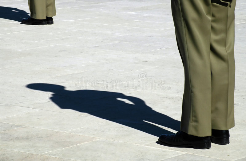 Soldier stood to attention. Legs and shadow of soldiers in khaki uniform stood to attention of parade ground royalty free stock image