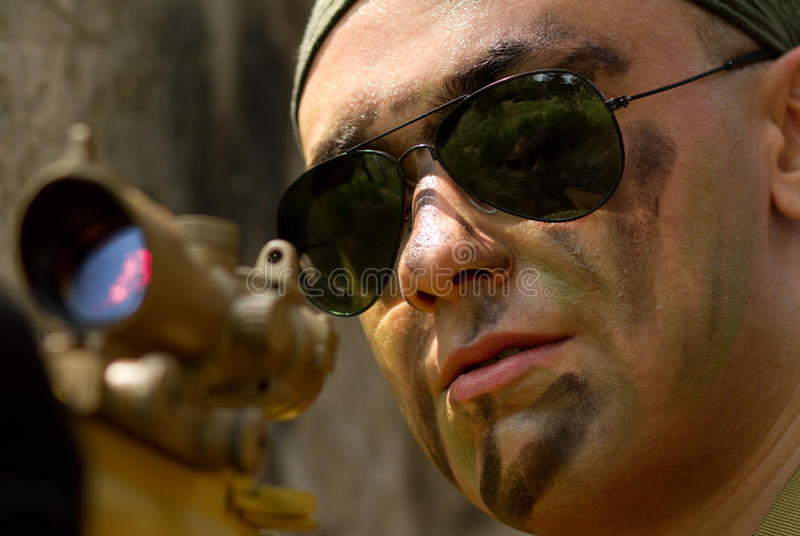 Soldier in sunglasses targeting with a gun royalty free stock images