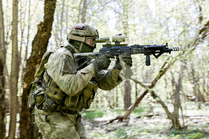 Soldier takes aim in forest stock photography