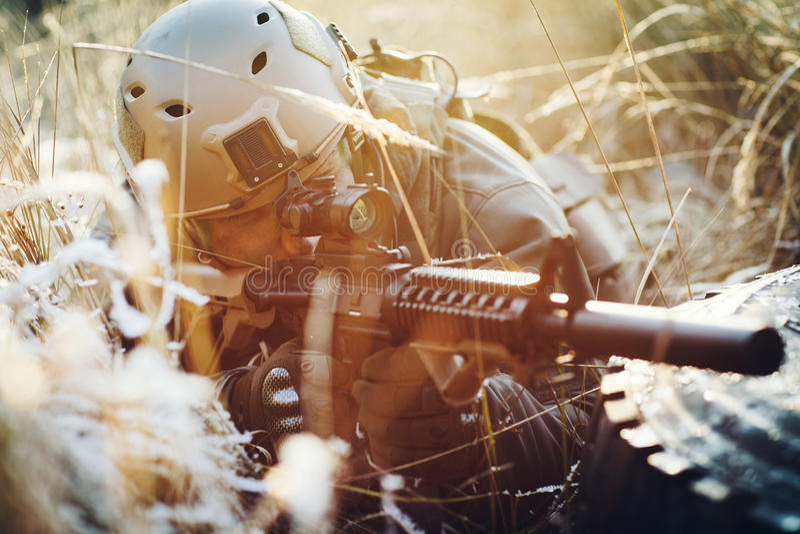 Soldier takes aim through the scope stock photos