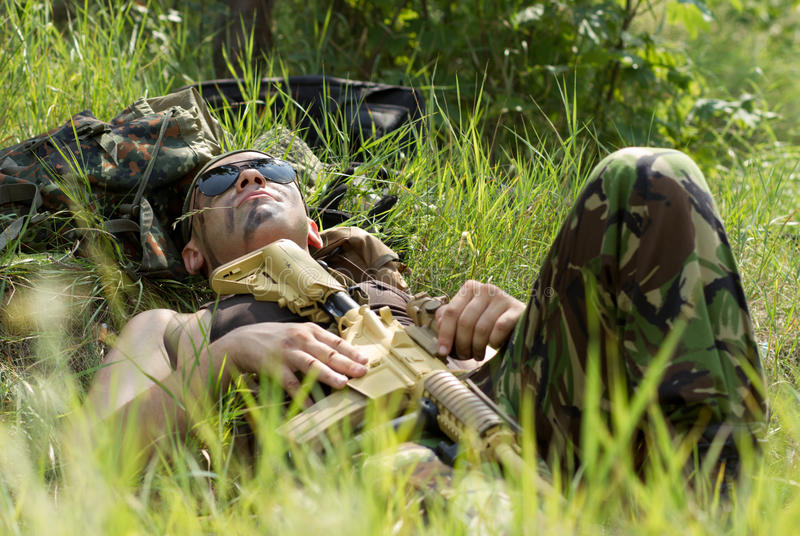 Soldier takes rest lying on a grass royalty free stock image