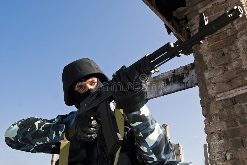 Soldier targeting with automatic rifle stock photography