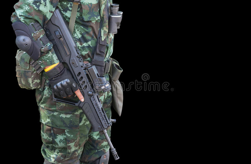 Soldier in uniform holding automatic assault rifle stock images
