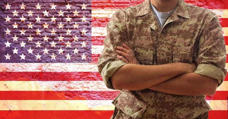 Soldier in an American military digital pattern uniform, standing on a USA flag background royalty free stock photos