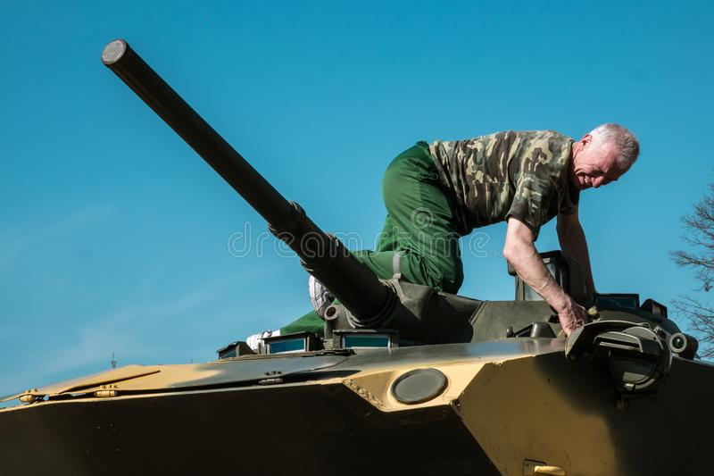 Soldier washes battle tank sitting on top of the tower.  stock photography