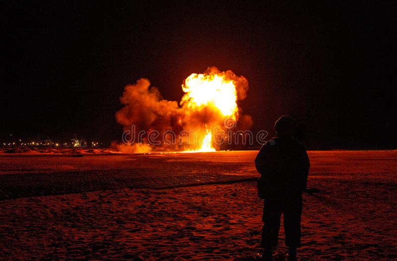 Soldier watches as bomb explosion goes off on the beach at night. Armed Forced Day in South Africa 2016 stock photography