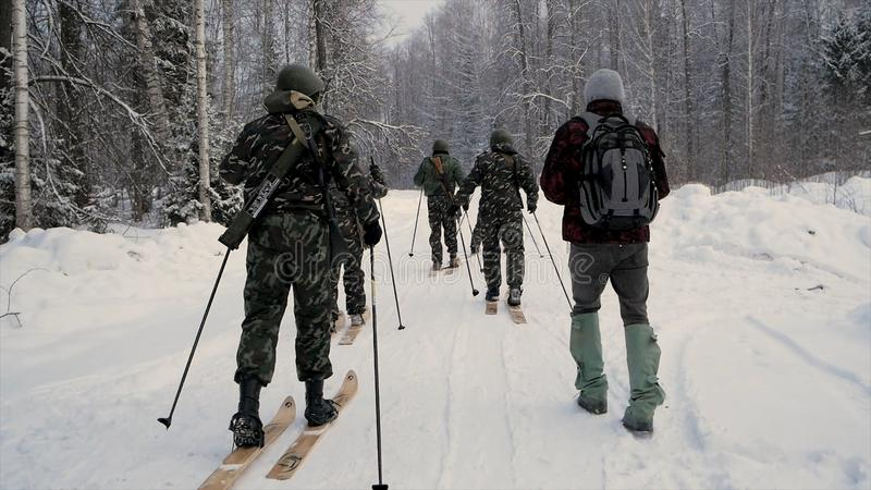 Soldier with weapons in cold forest. Winter warfare and military concept. Clip. Soldiers in winter forest on skis with royalty free stock photos