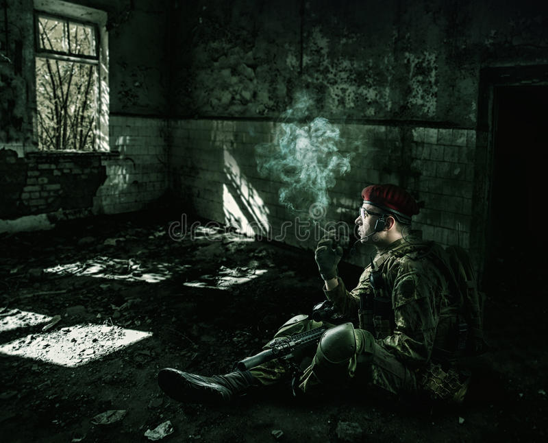 Soldier wearing military uniform in the destroyed building stock photography