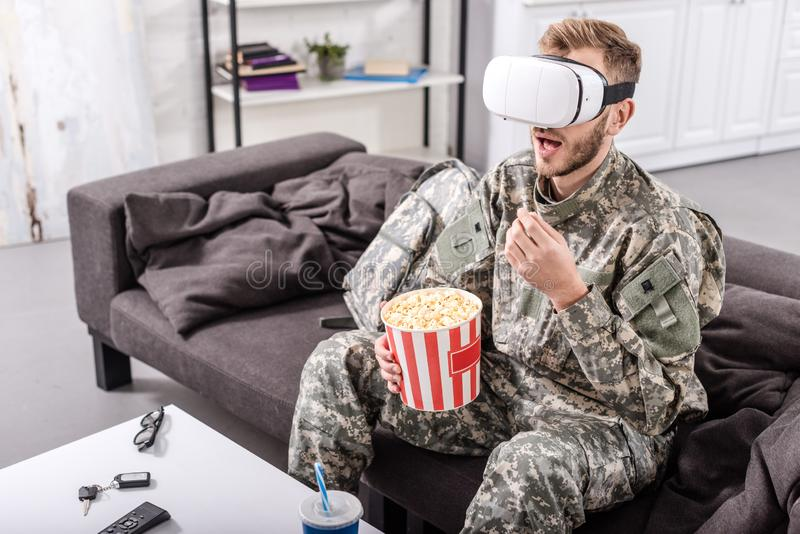 soldier wearing virtual reality headset, sitting on couch, watching movie and stock photo