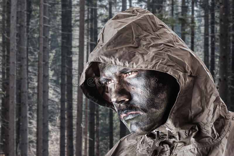 Soldier in the woods. A soldier wearing a poncho o raincoat and army camouflage face paint in a dark wood or forest royalty free stock photography